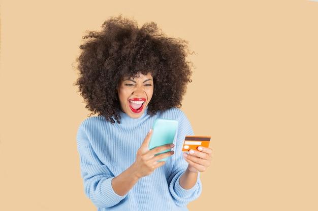Mooie afro-amerikaanse vrouw die online, mobiele telefoon en creditcard koopt