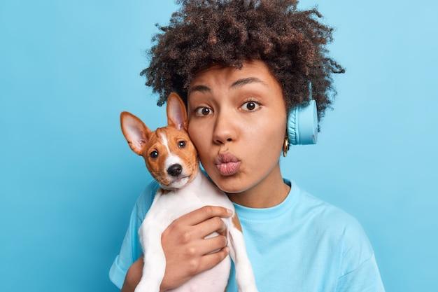 Mooie afro-amerikaanse vrouw draagt een hond van een klein ras in de buurt van het gezicht houdt de lippen gevouwen alsof ze iemand wil kussen die van haar favoriete huisdier houdt, terloops gekleed gaat, luistert naar muziek in een stereokoptelefoon