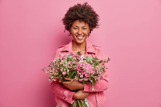 Mooie afro-amerikaanse vrouw drukt oprechte emoties uit, omhelst een boeket bloemen, heeft een lentestemming