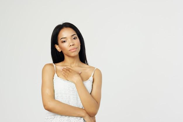 Mooie afro-amerikaanse vrouw in witte t-shirt aantrekkelijke look cosmetica