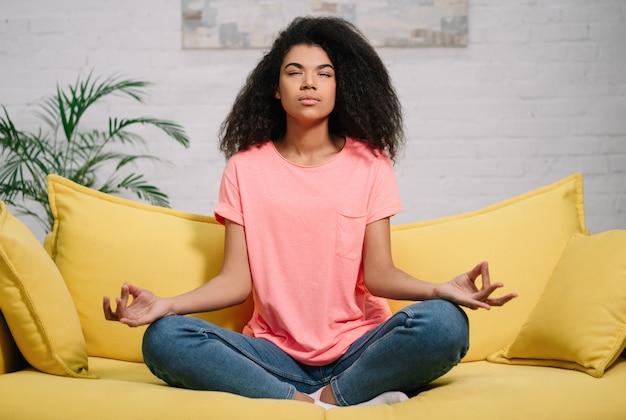 Mooie afro-amerikaanse vrouw meditatie, thuis blijven zitten in lotushouding, gezonde levensstijl. jong meisje beoefenen van yoga-oefeningen, ontspanning, zelfisolatie, quarantaine