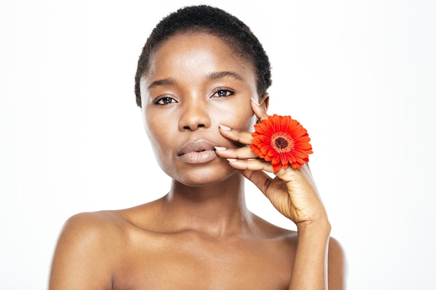 Mooie afro-amerikaanse vrouw met bloem kijken camera geïsoleerd op een witte achtergrond