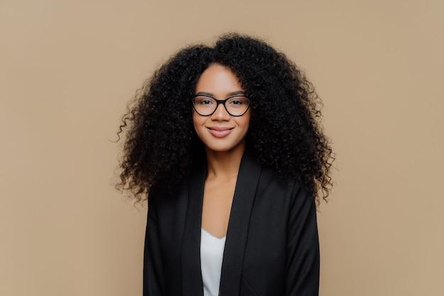 Mooie afro-amerikaanse vrouw met fris haar, gekleed in een elegant zwart jasje, transparante bril