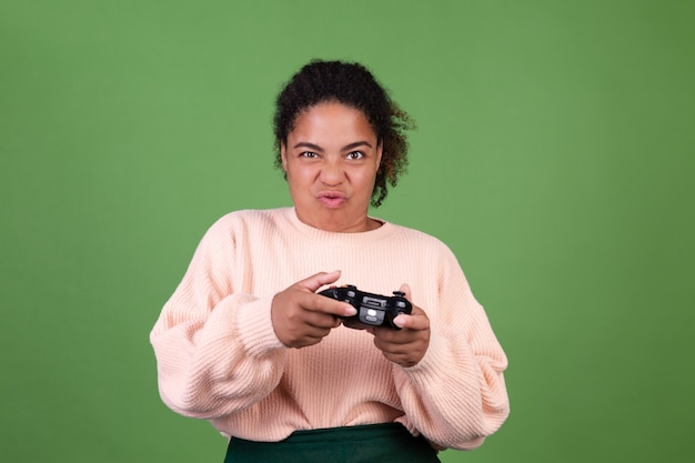 Mooie afro-amerikaanse vrouw op groene muur gericht op het spelen van videogames