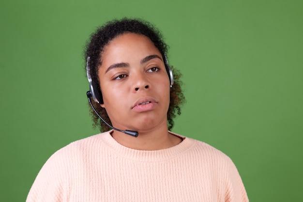 Mooie afro-amerikaanse vrouw op groene muur manager callcenter werknemer moe verveeld uitgeput