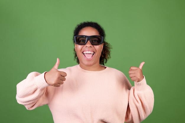 Mooie afro-amerikaanse vrouw op groene muur met 3d-bioscoopbril, gelukkig vrolijk positief, duimen omhoog