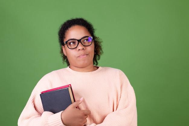 Mooie afro-amerikaanse vrouw op groene muur met notitieboekjes, studentleraar die een bril draagt, kijk bedachtzaam opzij
