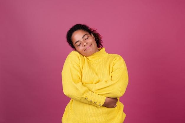 Mooie afro-amerikaanse vrouw op roze muur gelukkig lachend knuffelen zichzelf, hou van jezelf concept, zelfzorg