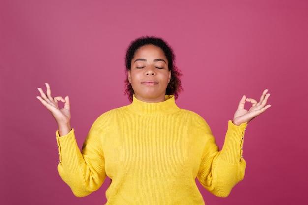 Mooie afro-amerikaanse vrouw op roze muur, gelukkig lachend, mediteer met gesloten ogen, hou van jezelf concept, zelfzorg