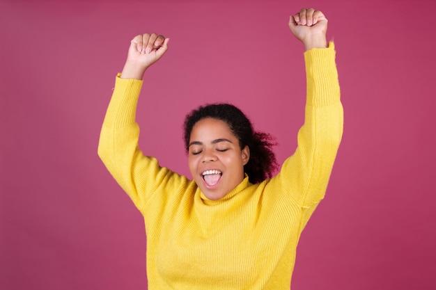 Mooie afro-amerikaanse vrouw op roze muur gelukkig lachend vrolijk positief dansend bewegend
