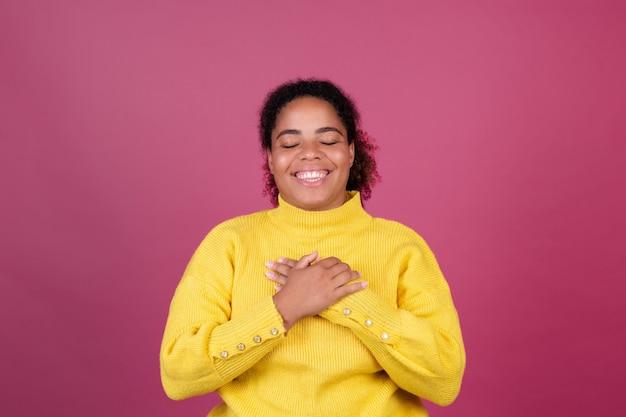 Mooie afro-amerikaanse vrouw op roze muur gelukkig lachende handen op borst hou van jezelf concept, zelfzorg