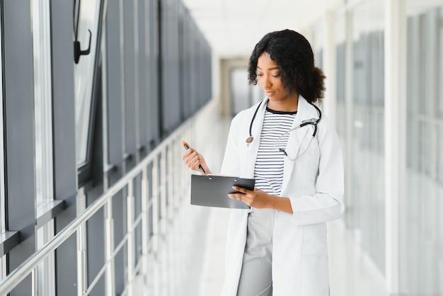 Mooie afro-amerikaanse vrouwelijke pediatrische verpleegster in modern kantoor