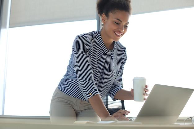 Mooie afro-amerikaanse zakenvrouw in slimme vrijetijdskleding die op laptop op kantoor werkt.