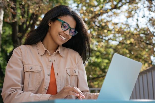 Mooie afro-amerikaanse zakenvrouw met behulp van laptop, trainingen kijken. succesvol bedrijfsconcept