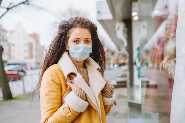 Mooie afro haired vrouw die beschermend medisch gezichtsmasker draagt ?? staat op de straat van de stad in de buurt van de etalage en kijkt naar de camera.