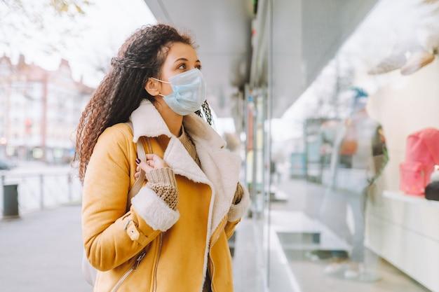 Mooie afro haired vrouw die beschermende medische gezichtsmasker draagt ?? staan op de straat van de stad en kijk naar de etalage.