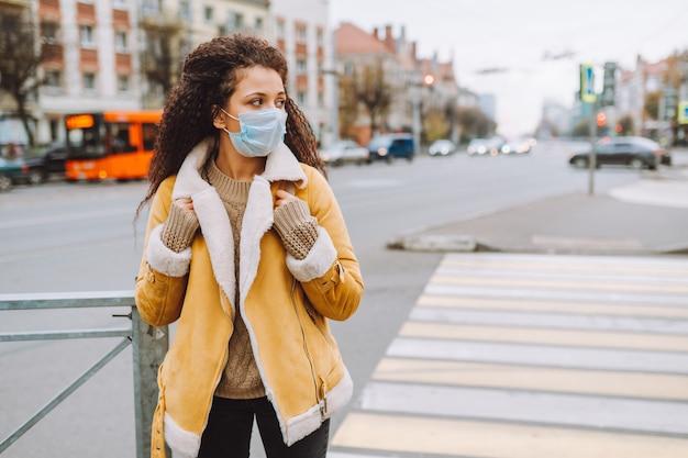 Mooie afro haired vrouw die beschermende medische gezichtsmasker draagt ?? staan op de straat van de stad. sociale afstand nemen, quarantaine.