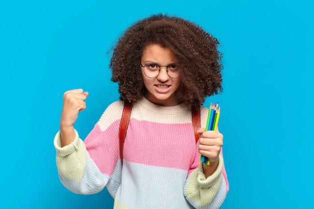 Mooie afro-tiener die agressief schreeuwt met een boze uitdrukking of met gebalde vuisten om succes te vieren. studentenconcept