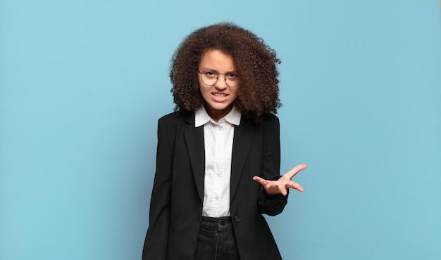 Mooie afro-tiener die boos, geïrriteerd en gefrustreerd schreeuwt wtf of wat er mis is met jou. humoristisch bedrijfsconcept