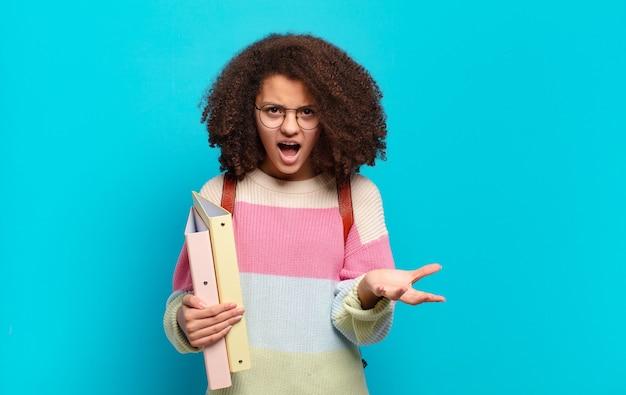 Mooie afro-tiener die boos, geïrriteerd en gefrustreerd schreeuwt wtf