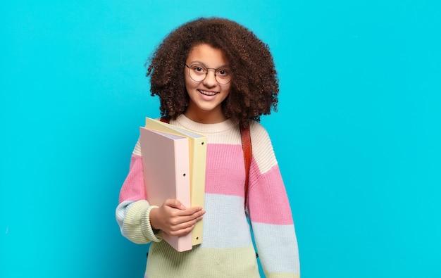 Mooie afro-tiener die er blij en aangenaam verrast uitziet, opgewonden met een gefascineerde en geschokte uitdrukking. student concept