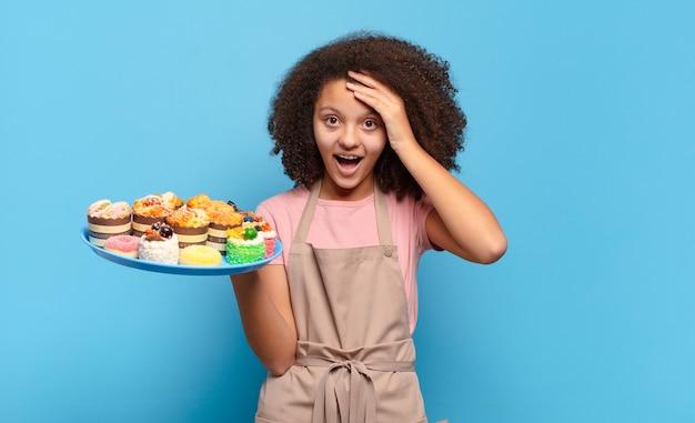 Mooie afro-tiener die er blij, verbaasd en verrast uitziet, glimlacht en verbazingwekkend en ongelooflijk goed nieuws realiseert. humoristisch bakkersconcept