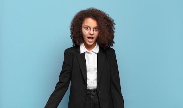 Mooie afro-tiener die erg geschokt of verrast kijkt, starend met open mond en zegt wow.
