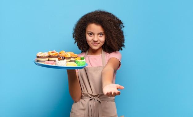 Mooie afro-tiener die gelukkig glimlacht met een vriendelijke, zelfverzekerde, positieve blik, een object of concept aanbiedt en toont. humoristisch bakkersconcept Premium Foto