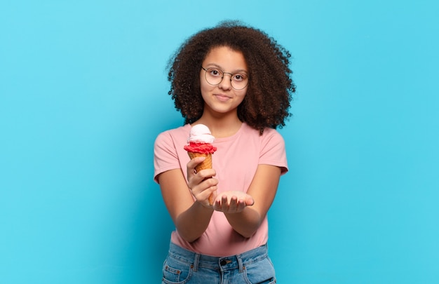 Mooie afro-tiener die gelukkig glimlacht met vriendelijke, zelfverzekerde, positieve blik, die een voorwerp of concept aanbiedt en toont. sumer ijs concept