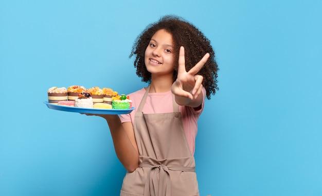 Mooie afro-tiener die gelukkig, zorgeloos en positief glimlacht en kijkt, met één hand overwinning of vrede gebaart. humoristisch bakkersconcept