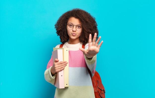 Mooie afro-tiener die lacht en er vriendelijk uitziet, nummer vijf of vijfde toont met de hand naar voren, aftellend. studentenconcept