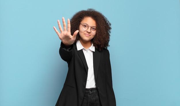 Mooie afro-tiener die lacht en er vriendelijk uitziet, nummer vijf of vijfde toont met de hand naar voren, aftellend