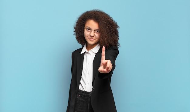 Mooie afro-tiener die trots en zelfverzekerd glimlacht en nummer één triomfantelijk poseert