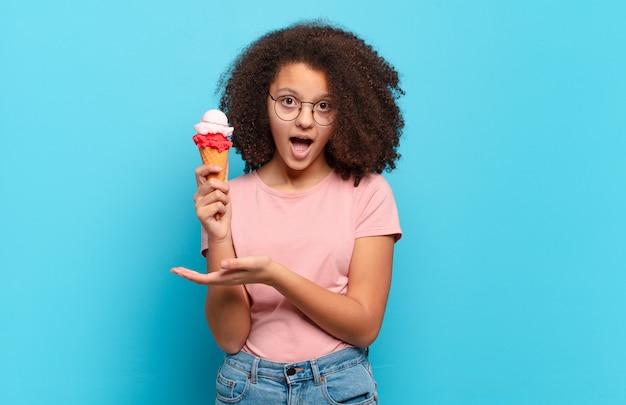 Mooie afro-tiener die verrast en geschokt kijkt, met open mond terwijl hij een object vasthoudt met een open hand aan de zijkant