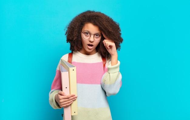 Mooie afro-tiener die verrast, met open mond en geschokt kijkt, een nieuwe gedachte beseft