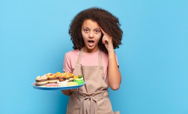 Mooie afro-tiener die verrast, met open mond, geschokt kijkt en een nieuwe gedachte, idee of concept realiseert. humoristisch bakkersconcept