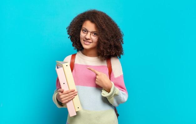 Mooie afro-tiener die vrolijk lacht, zich gelukkig voelt en naar de zijkant en naar boven wijst, object in kopie ruimte toont. student concept