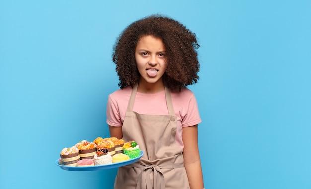 Mooie afro-tiener die walgt en geïrriteerd voelt, tong uitsteekt, een hekel heeft aan iets smerigs en vies. humoristisch bakkersconcept