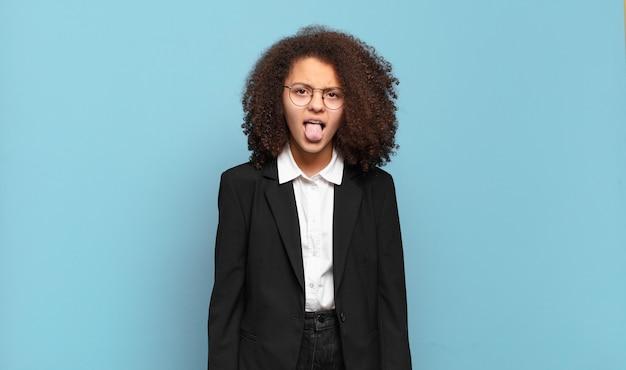 Mooie afro-tiener die walgt en geïrriteerd voelt, tong uitsteekt, niet van iets smerigs en vies houdt. humoristisch bedrijfsconcept