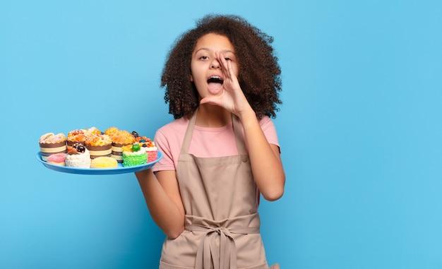 Mooie afro-tiener die zich blij, opgewonden en positief voelt, een grote schreeuw geeft met handen naast de mond, roept