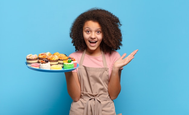 Mooie afro-tiener die zich blij, opgewonden, verrast of geschokt voelt, glimlacht en verbaasd is over iets ongelooflijks