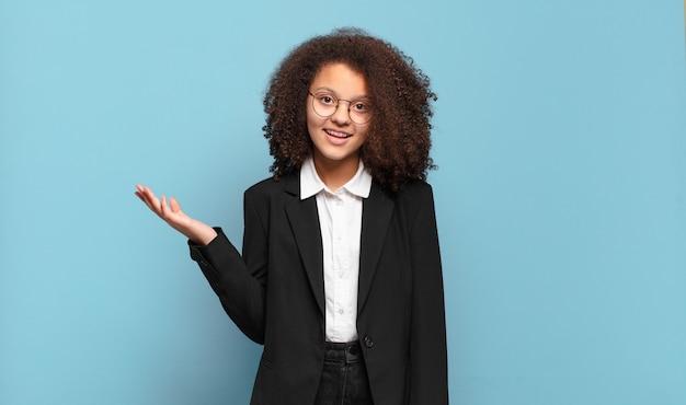 Mooie afro-tiener die zich blij, verrast en opgewekt voelt, lacht met een positieve instelling, een oplossing of idee realiseert. humoristisch bedrijfsconcept