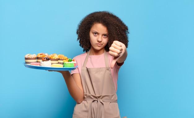 Mooie afro-tiener die zich boos, boos, geïrriteerd, teleurgesteld of ontevreden voelt, duimen naar beneden laat zien met een serieuze blik. humoristisch bakkersconcept