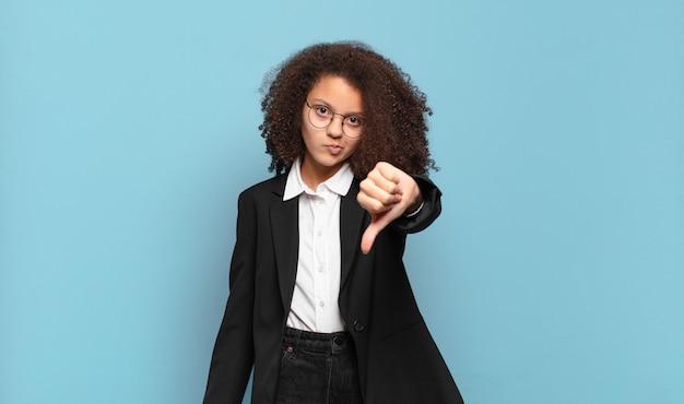 Mooie afro-tiener die zich boos, boos, geïrriteerd, teleurgesteld of ontevreden voelt, duimen naar beneden met een serieuze blik. humoristisch bedrijfsconcept