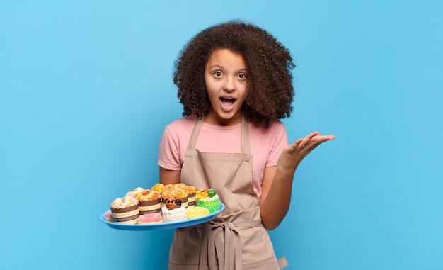 Mooie afro-tiener die zich extreem geschokt en verrast, angstig en in paniek voelt, met een gestreste en met afschuw vervulde blik. humoristisch bakkersconcept
