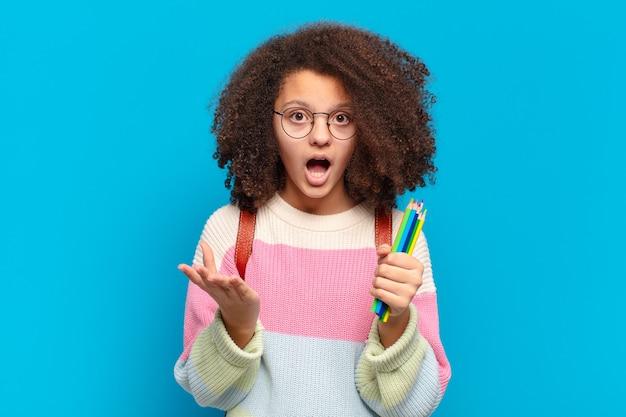 Mooie afro-tiener die zich extreem geschokt en verrast, angstig en in paniek voelt, met een gestreste en met afschuw vervulde blik. student concept