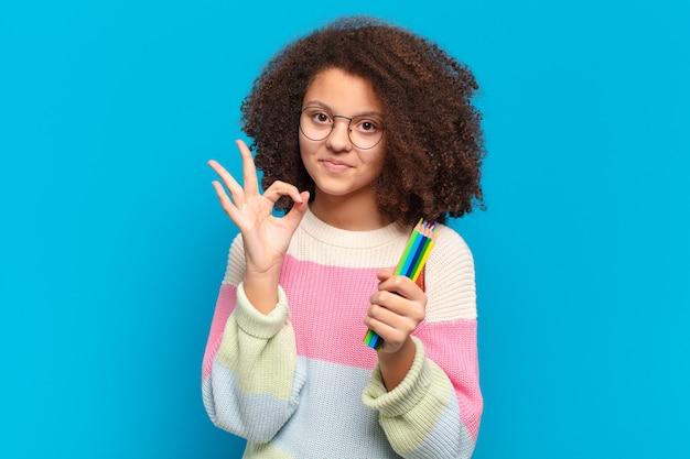 Mooie afro-tiener die zich gelukkig, ontspannen en tevreden voelt, goedkeuring toont met een goed gebaar, glimlachend. student concept