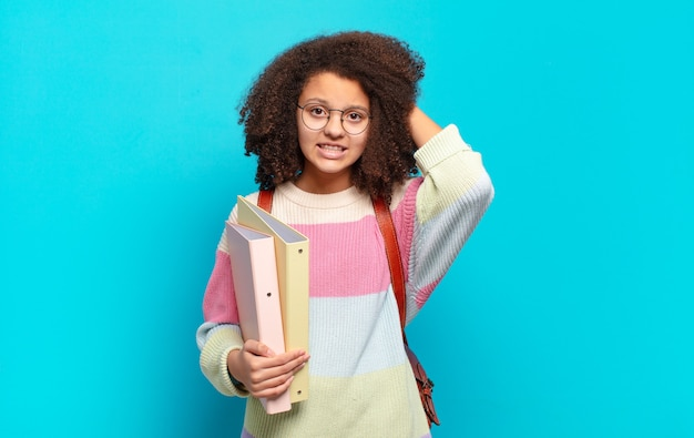 Mooie afro-tiener die zich gestrest, bezorgd, angstig of bang voelt, met de handen op het hoofd, in paniek bij vergissing