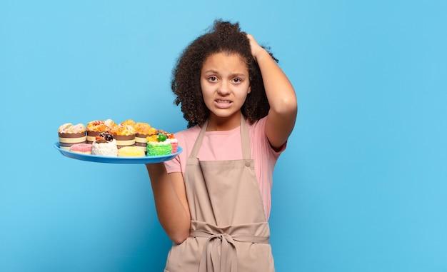 Mooie afro-tiener die zich gestrest, bezorgd, angstig of bang voelt, met de handen op het hoofd, in paniek raakt bij vergissing. humoristisch bakkersconcept
