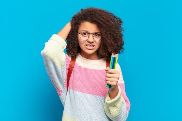 Mooie afro-tiener die zich gestrest, bezorgd, angstig of bang voelt, met de handen op het hoofd, in paniek raakt bij vergissing. student concept